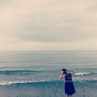 水の体の横に立っている人の写真・画像素材[715796]