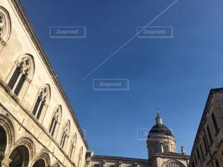 建物の側に時計と大きな背の高い塔の写真・画像素材[716935]