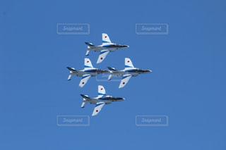 澄んだ青い空を飛んでいるジェット戦闘機の写真・画像素材[719560]