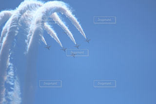 それから出てくる煙と空を飛んでいる飛行機の写真・画像素材[719562]