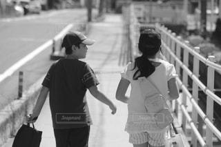 フェンスの横にある道を歩いている女性の写真・画像素材[775398]
