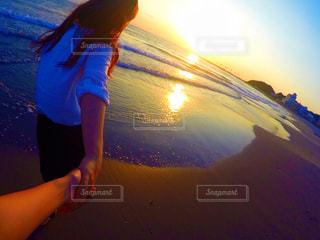 背景の夕日と女性の写真・画像素材[721346]