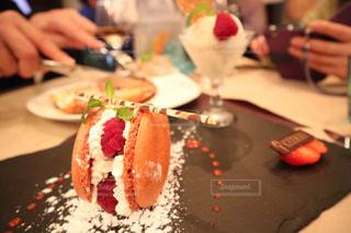 皿の上のケーキをテーブルに座っている人々 のグループの写真・画像素材[1035736]