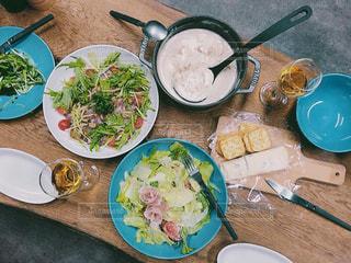 食品のプレートをテーブルに座っている女性の写真・画像素材[850188]