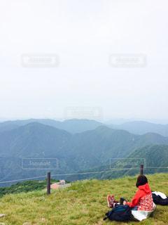 山の上に座っている女の写真・画像素材[727135]