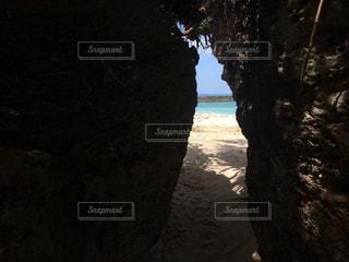 岩の隙間から見えるエメラルドグリーンビーチの写真・画像素材[1129722]