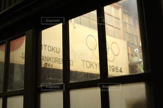 大きな窓の奥に東京オリンピック(1964年)の看板の写真・画像素材[726305]