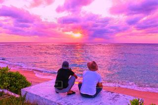 男と女の水の体の横に座っています。 - No.727836