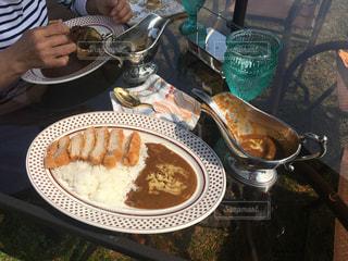 食品のプレートをテーブルに着席した人の写真・画像素材[1105479]