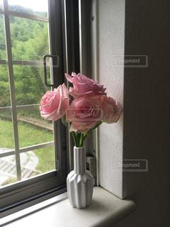 花の花瓶が窓の前で座っています。の写真・画像素材[731709]