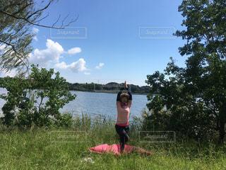 木の隣に立っている若い女の子の写真・画像素材[763087]