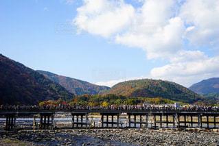 背景の山が付いている水の体の上の橋の写真・画像素材[892425]
