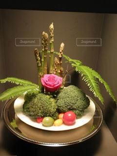 テーブルの上の花の花瓶をのせた白プレート - No.740498