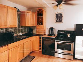 ステンレス鋼の電気器具、木製キャビネットを備えたキッチンの写真・画像素材[736878]