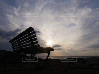 夕暮れ時の海を見下ろすベンチの写真・画像素材[934782]