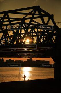 夕方川岸で犬の散歩の写真・画像素材[938527]
