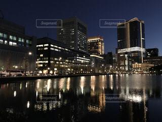 オフィスの街明かりを照らす池の水面の写真・画像素材[943664]