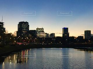 国会議事堂とオフィスビルの明かりを照らす皇居のお堀池の写真・画像素材[943666]