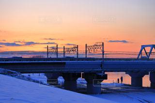 積雪の朝に鉄橋を渡る電車の写真・画像素材[975127]
