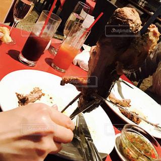 食品のプレートをテーブルに座っている女性の写真・画像素材[742298]