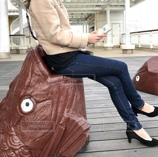 座ってスマートフォンを触る女性の写真・画像素材[865958]