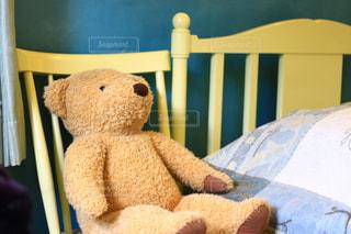ベッド脇の椅子に座っているテディベアの写真・画像素材[1430181]