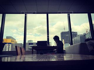 窓の前のテーブルに座っている人々 のグループの写真・画像素材[740203]