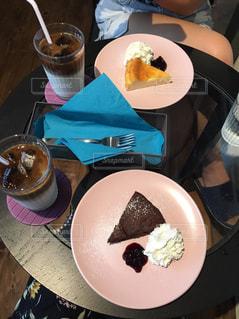 食品のプレートをテーブルに座っている女性 - No.741122