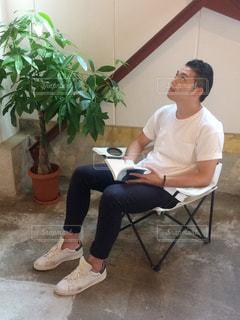 椅子に座って本を読んでいる人の写真・画像素材[2502690]