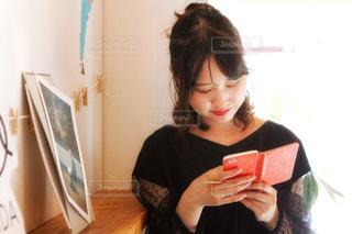カフェで携帯をさわる女性の写真・画像素材[2611023]