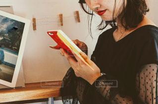 携帯を持つ紅い口紅の女性の写真・画像素材[2611033]