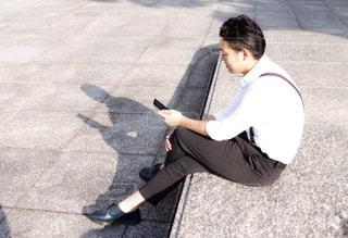 スマホいじりをするスーツ姿の男性の写真・画像素材[2674545]