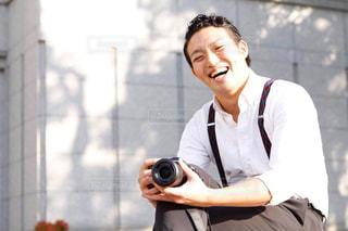 カメラを持つスーツ姿の笑顔の男性の写真・画像素材[2675153]