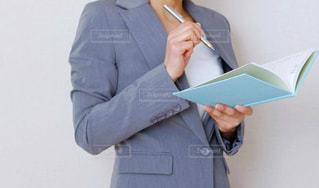 ペンとノートを持っているスーツ姿の女性の手の写真・画像素材[2729189]
