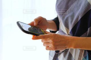 スマホいじりをするエプロンを着た女性の手の写真・画像素材[2729416]
