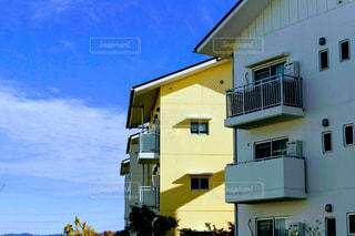 晴れた空と黄色と白のマンションの写真・画像素材[2755047]
