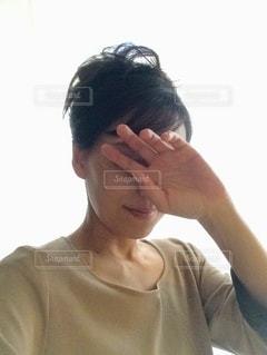 顔を手で隠している女性の写真・画像素材[3460270]