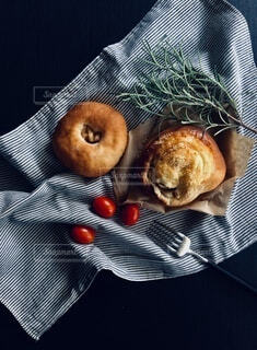 布の上のパンとトマトとフォークとローズマリーの写真・画像素材[3676782]