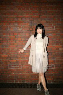 レンガ壁の前に立っている女性 - No.742862