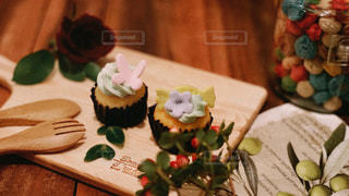 テーブルの上のケーキと木製のまな板の写真・画像素材[1275404]