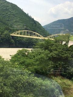 背景の山が付いている水の体の上の橋の写真・画像素材[744639]