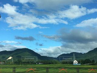 フィールドの背景の山と人々 のグループの写真・画像素材[744652]