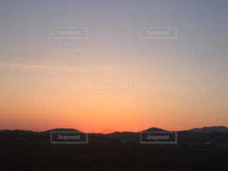 背景の山が付いている水の体に沈む夕日の写真・画像素材[755060]