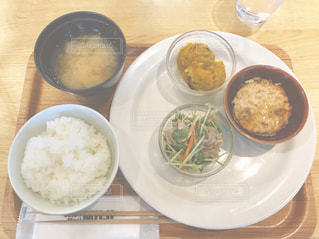 テーブルの上の皿の上に食べ物のボウルの写真・画像素材[744799]