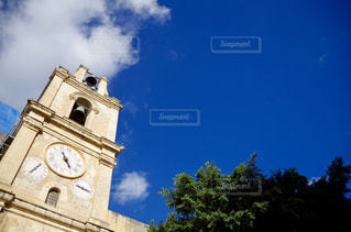 曇りの青い空の下に座って背の高い時計塔の写真・画像素材[1049506]