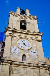 建物の側に時計と大きな背の高い塔の写真・画像素材[1049509]