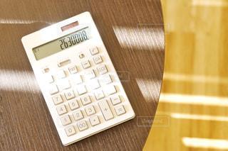電卓とテーブルの写真・画像素材[1829086]