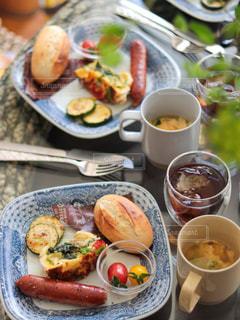 食べ物の皿をテーブルの上に置くの写真・画像素材[3171495]