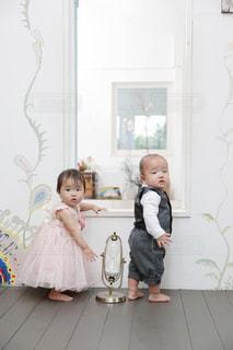 つかまり立ちしながら振り返る双子の赤ちゃんの写真です。の写真・画像素材[835439]