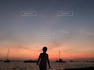 バック グラウンドで夕焼けのビーチに立っている人の写真・画像素材[748589]